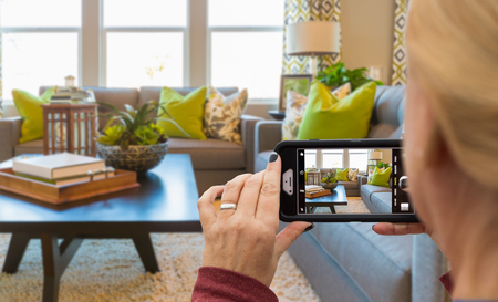 Woman Taking Pictures of A Living Room in Model Home with Her Smart Phone. Фото со стока