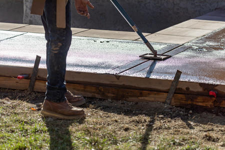 Construction Worker Smoothing Wet Cement With Long Handled Edger Tool