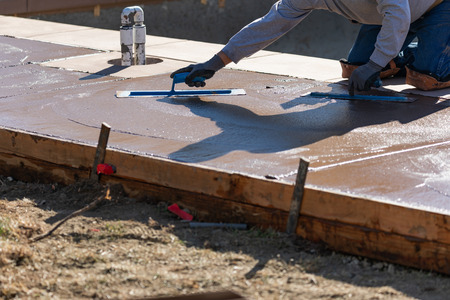 Construction Worker Smoothing Wet Cement With Trowel Tools