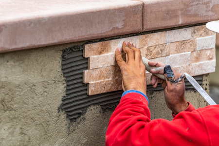Worker Installing Wall Tile at Construction Site. Imagens