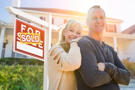Attraktives Ehepaar mittleren Alters im Vorderhaus und verkauftes Immobilienschild.
