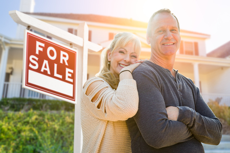 Attractive Middle-aged Couple In Front House and For Sale Real Estate Sign. Standard-Bild