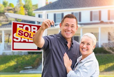 Pareja feliz con las llaves de la casa nueva delante del cartel de bienes raíces vendidos y hermosa casa. Foto de archivo