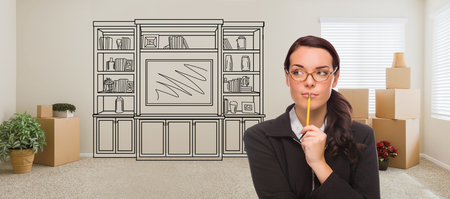 Woman Inside Room With Moving Boxes Glancing Toward Entertainment Unit Drawing on Wall.