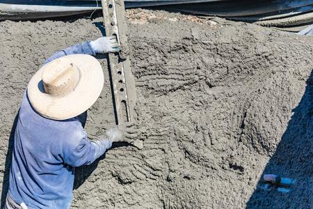 Poolbauarbeiter, der mit einer glatteren Stange auf nassem Beton arbeitet