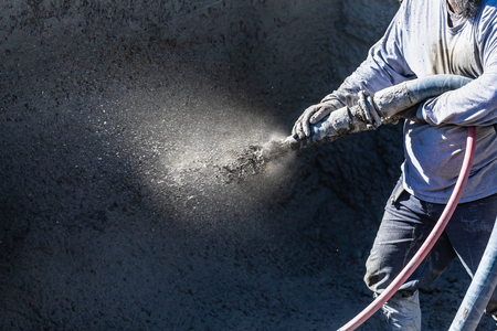 Pool Construction Worker Shooting Concrete, Shotcrete or Gunite Through Hose Stockfoto