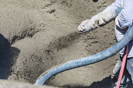 Pool Construction Worker Shooting Concrete, Shotcrete or Gunite Through Hose Stock fotó