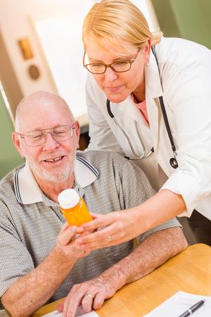 Doctor or Nurse Explaining Prescription Medicine to Attentive Senior Man.