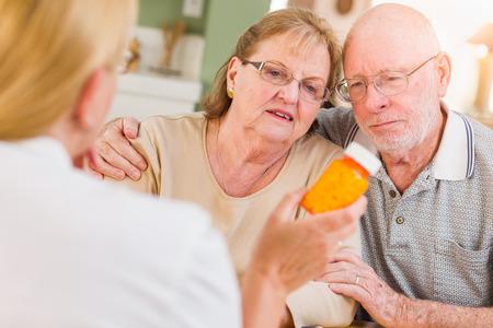 Doctor or Nurse Explaining Prescription Medicine to Senior Adult Couple.