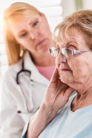 Melancholy Senior Adult Woman Being Consoled by Female Doctor or Nurse. Stock Photo