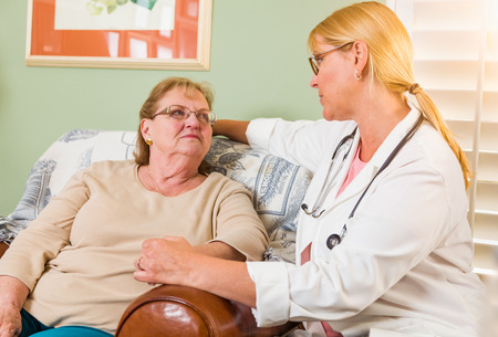 Happy Smiling Doctor or Nurse Talking to Senior Woman in Chair At Home.