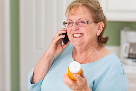 Senior Adult Woman on Cell Phone Holding Prescription Bottle. Imagens