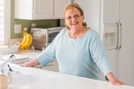 Portrait of A Beautiful Smiling Senior Adult Woman in Kitchen.