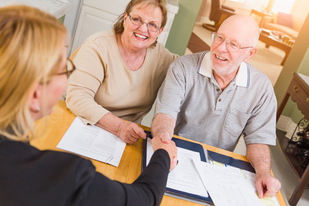 Senior Adult Couple Going Over Documents in Their Home with Agent At Signing.