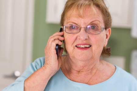 Happy Senior Adult Woman on Her Smart Cell Phone in Kitchen. Stock Photo