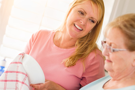Senior Adult Woman and Young Daughter Talking At Sink in Kitchen. Stock Photo