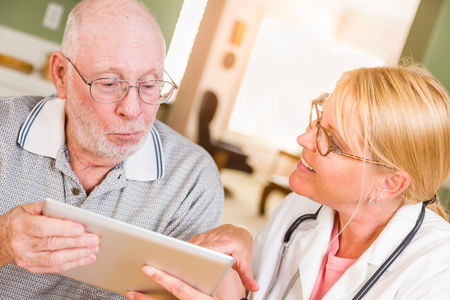 Female Doctor or Nurse Showing Senior Man Touch Pad Computer At Home.