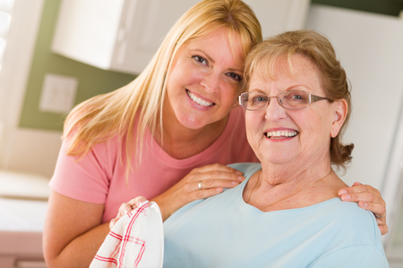 Portrait of Smiling Senior Adult Woman and Young Daughter At Sink in Kitchen.