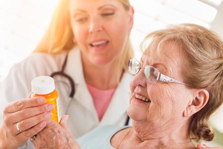 Happy Female Doctor or Nurse Explaining Prescription to Senior Adult Woman.