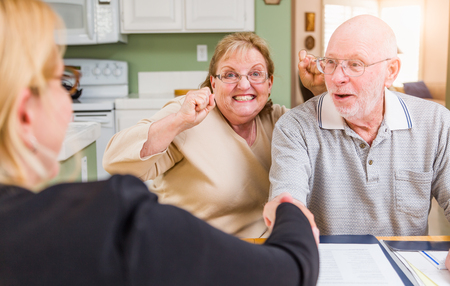 Senior Adult Couple Celebrating Over Documents in Their Home with Agent At Signing.
