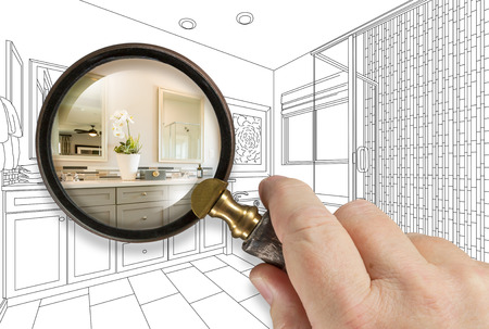 Hand Holding Magnifying Glass Revealing Custom Bathroom Design Drawing and Photo Combination. Imagens - 124889234