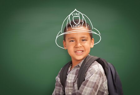 Young Hispanic Student Boy Wearing Backpack Front Of Blackboard with Fireman Helmet Drawn In Chalk Over Head.