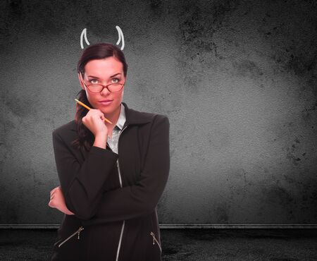 Devil Horns Drawn on Head of Red Faced Young Adult Woman with Pencil In Front of Grungy Wall with Copy Space.
