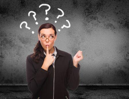 Marques de question dessinées au-dessus de la tête d'une jeune femme adulte devant le mur avec espace de copie.