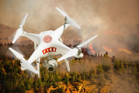 Fire Department Unmanned Aircraft System, (UAS) Drone Isolated Above a Forest Fire.
