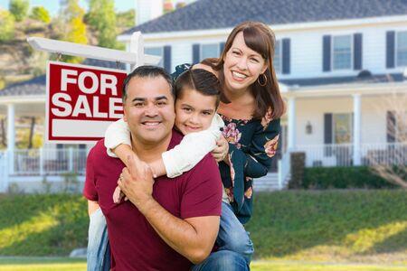 Feliz familia de raza mixta en frente de la casa y venta inmobiliaria firmar.