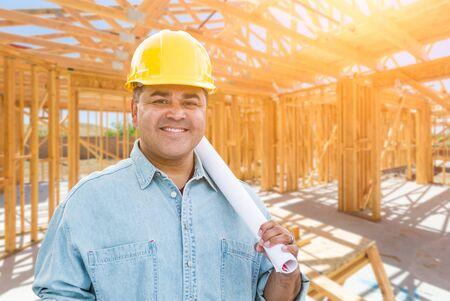 Hispanischer männlicher Auftragnehmer mit Blaupausen-Plänen mit Schutzhelm auf der Baustelle.