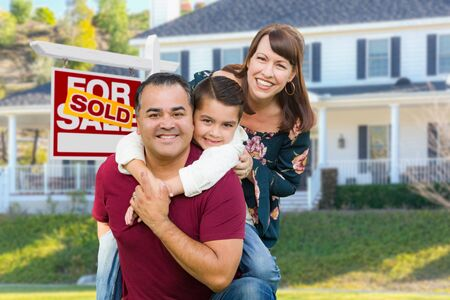 Happy Mixed Race Family In Front of House and Sold For Sale Real Estate Sign.