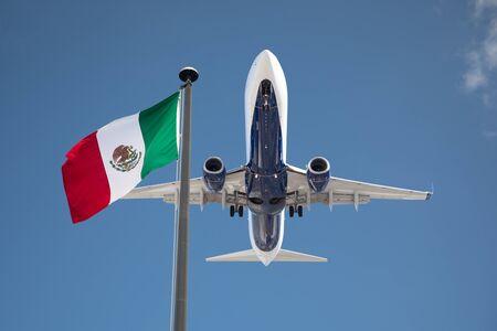 Vue de dessous de l'avion de passagers survolant le Mexique en agitant le drapeau sur le poteau.