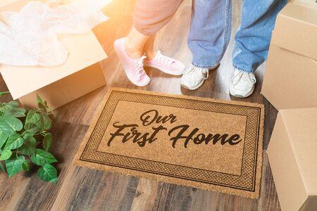 Homme et femme déballant près de notre premier tapis de bienvenue, boîtes de déménagement et plante. Banque d'images