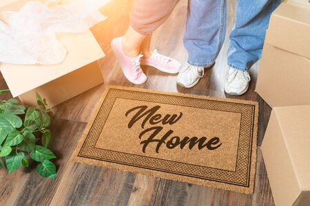 Man and Woman Unpacking Near New Home Welcome Mat
