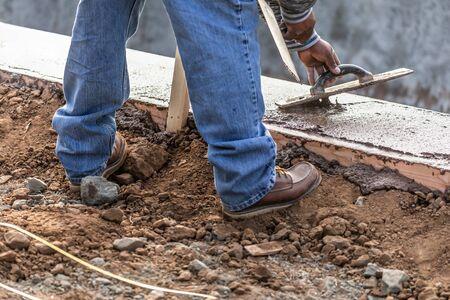 Trabajador de la construcción con paleta de madera sobre cemento húmedo formando Coping alrededor de la nueva piscina. Foto de archivo
