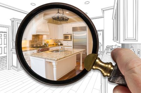 Hand Holding Magnifying Glass Revealing Finished Kitchen Build Over Drawing. Stockfoto