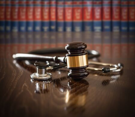 Gavel and Stethoscope on Wooden Table With Law Books In Background.