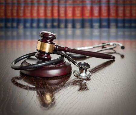 Gavel and Stethoscope on Wooden Table With Law Books In Background. Stock Photo