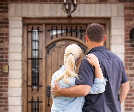 Happy Young Couple Facing Front Door of New House.