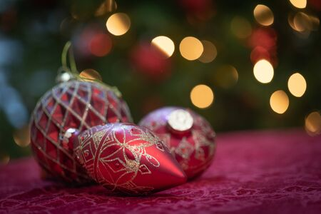 Elaborate Christmas Ornaments Resting on Table In Front of Lit Tree.