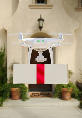 Drone Delivering Red Ribbon Wrapped Package to House Porch. Stock Photo