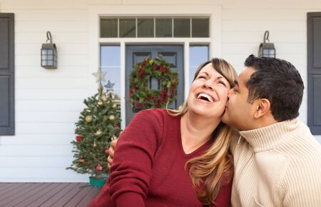 Hispanic and Caucasian Young Adult Couple On Christmas Decorated Front Porch of House. Banque d'images