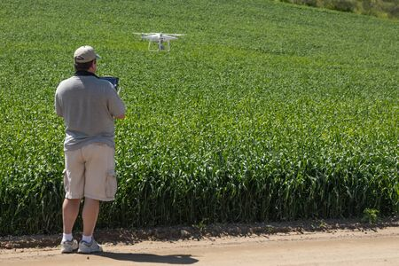 Pilot Flying Unmanned Aircraft Drone Gathering Data Over Country Farmland Field. Foto de archivo