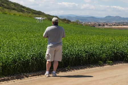 Pilot Flying Unmanned Aircraft Drone Gathering Data Over Country Farmland Field.