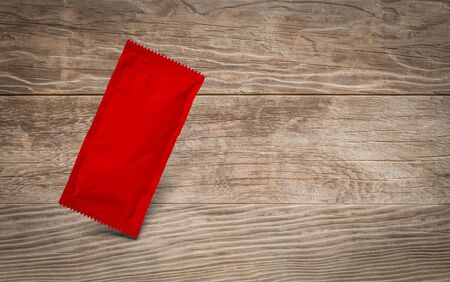 Blank Red Condiment Packet Floating on Aged Wood Background. Archivio Fotografico - 137640107
