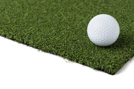 Golf Ball Resting on Section of Artificial Turf Grass On White Background.