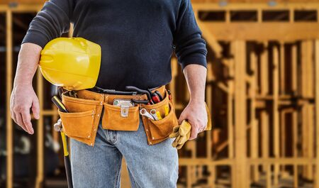 Contractor With Tool Belt and Hard Hat In Front of Wood Framing Construction Site.