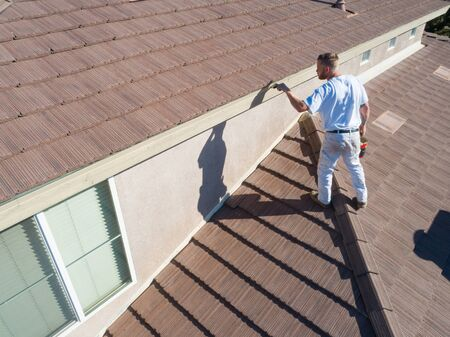 Professional Painter Using A Brush to Paint House Fascia.
