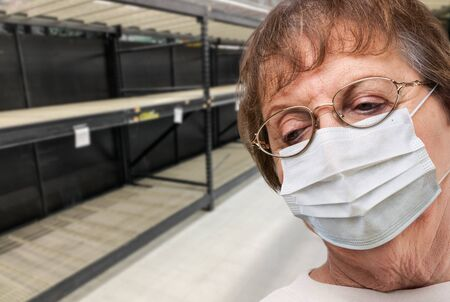 Senior Adult Woman In Medical Face Mask Walking Down Empty Aisle of Grocery Store.